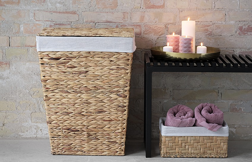Laundry basket and bench with candles in a bathroom. Basket with towels
