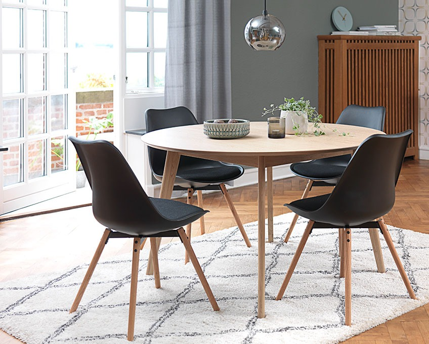 Round dining table and black dining chairs on a rug in a dining room
