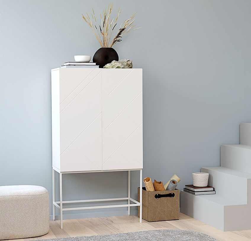 White cabinet with a black vase and other décor, a white pouffe and a storage basket in jute